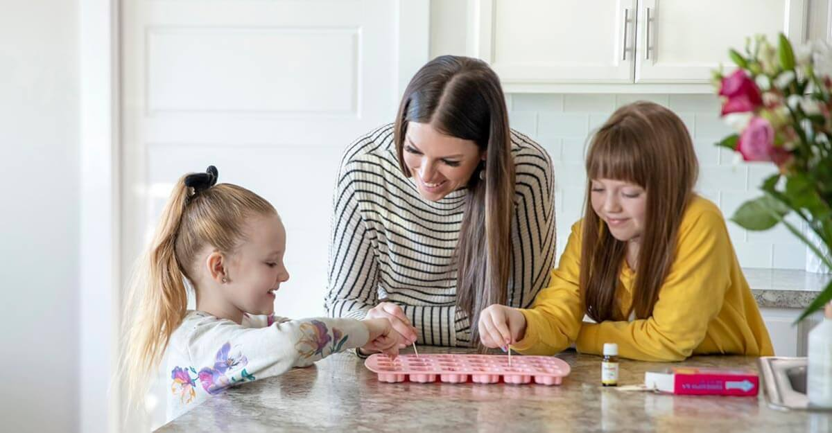 Mother making DIY scented crayons with her kids