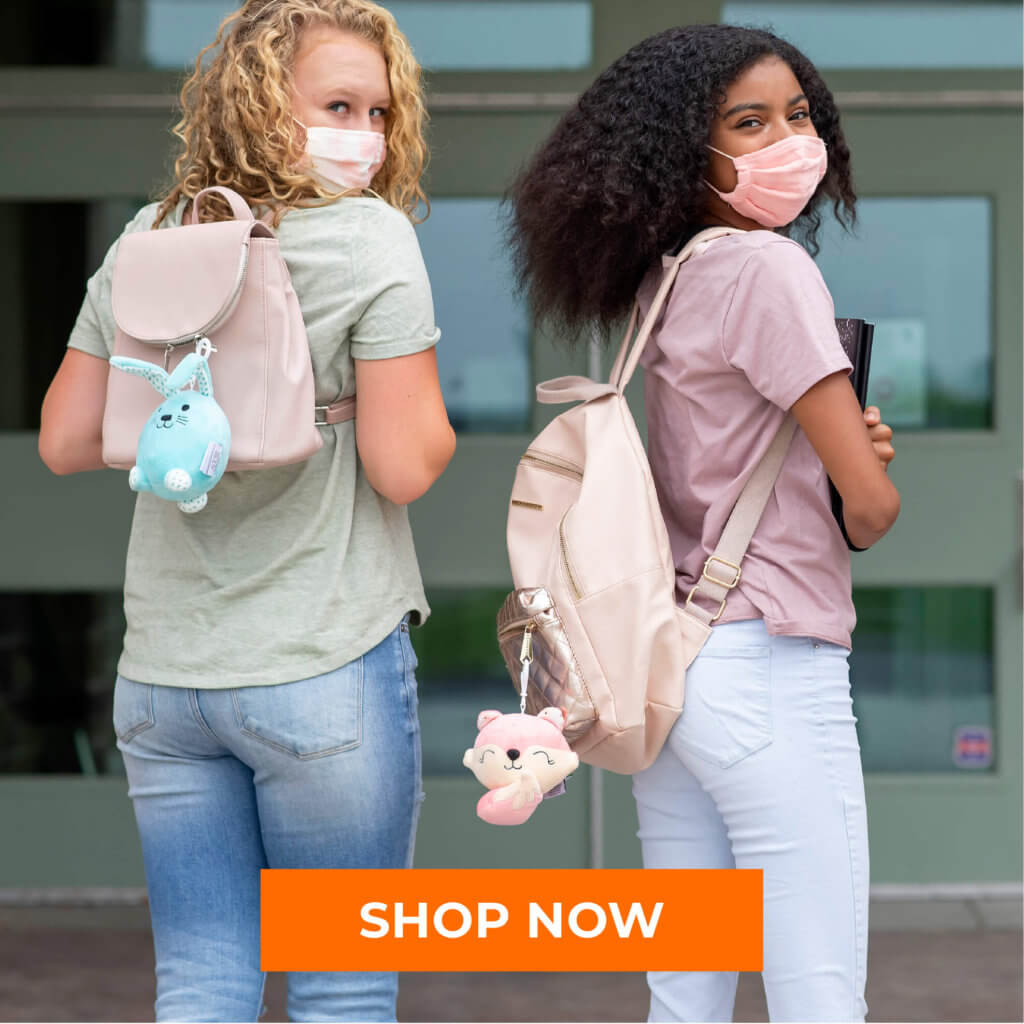 Young girls wearing masks with aroma plush pal clips on their backpacks