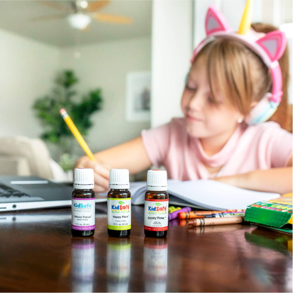 Young girl doing homework at the table with KidSafe essential oil blends