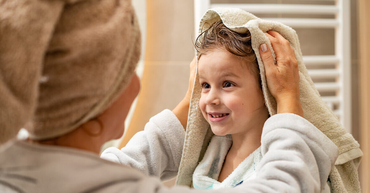 Woman helping dry her child's hair after bathtime