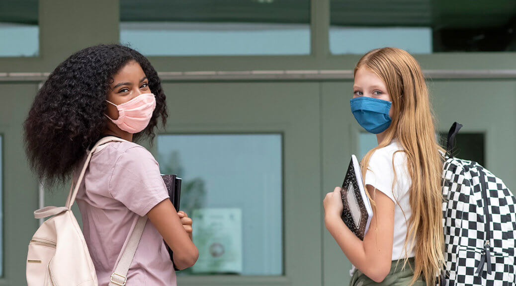 Young girls wearing face masks to school