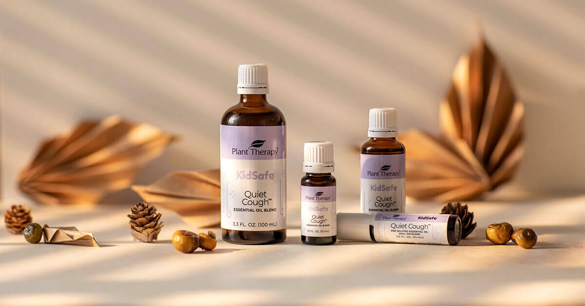 Quiet Cough Essential Oil in multiple sizes with paper décor in the background