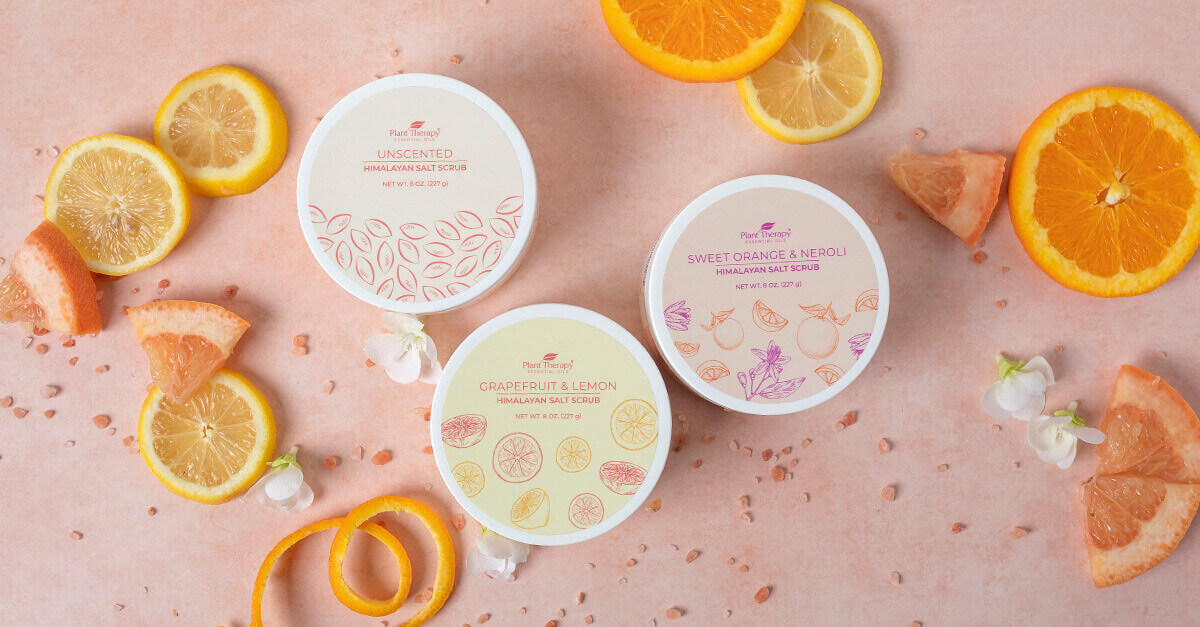All three salt scrubs on a pink background with citrus slices surrounding