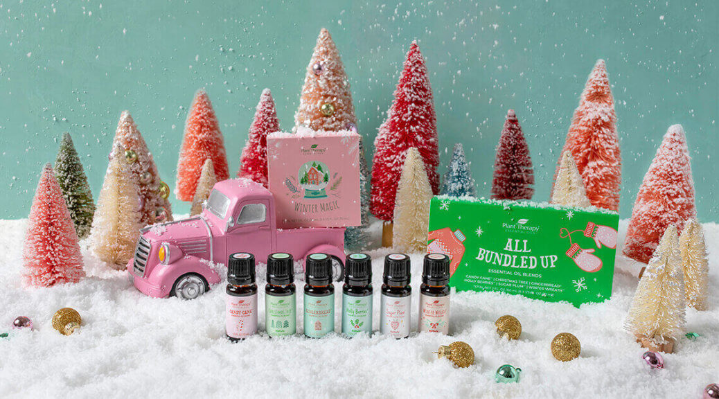 fake Christmas trees in fluffy snow. All Bundled Up Essential Oil Set in a standing line