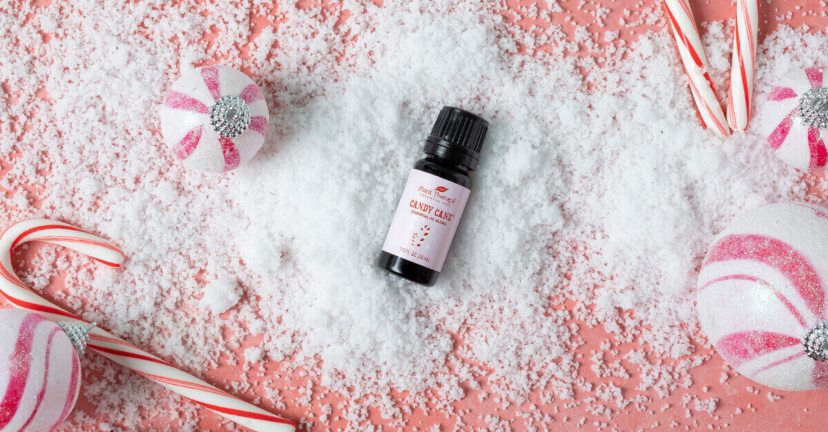 Candy cane essential oil blend with fake snow and real candy canes surrounding it