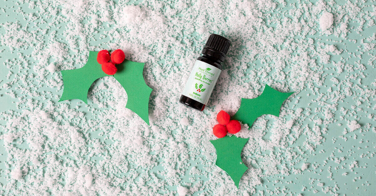 Holly berries essential oil blend laying on fake snow and paper holly berries