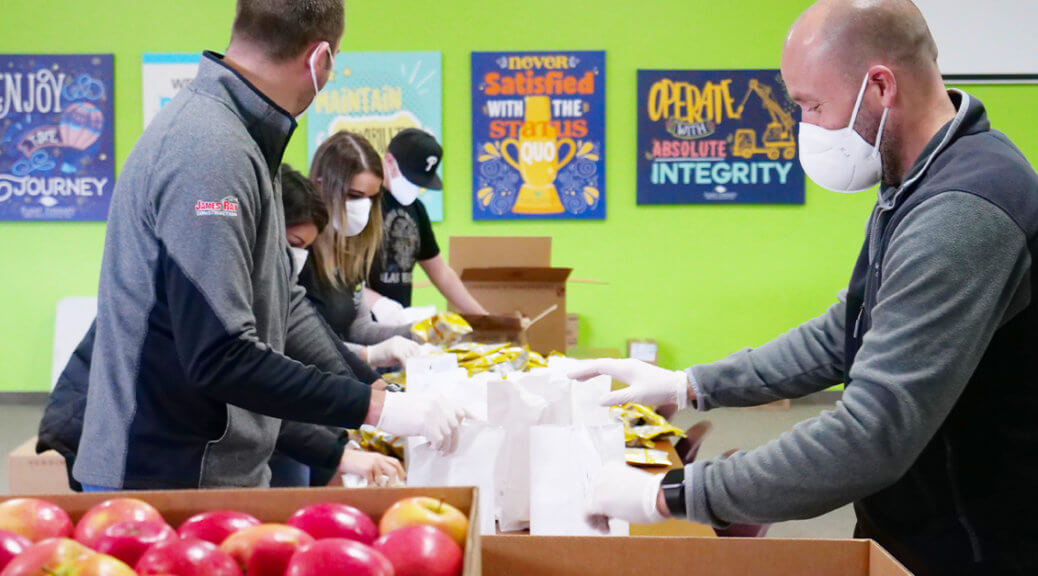 a line of employees in masks, building sack lunches on a table