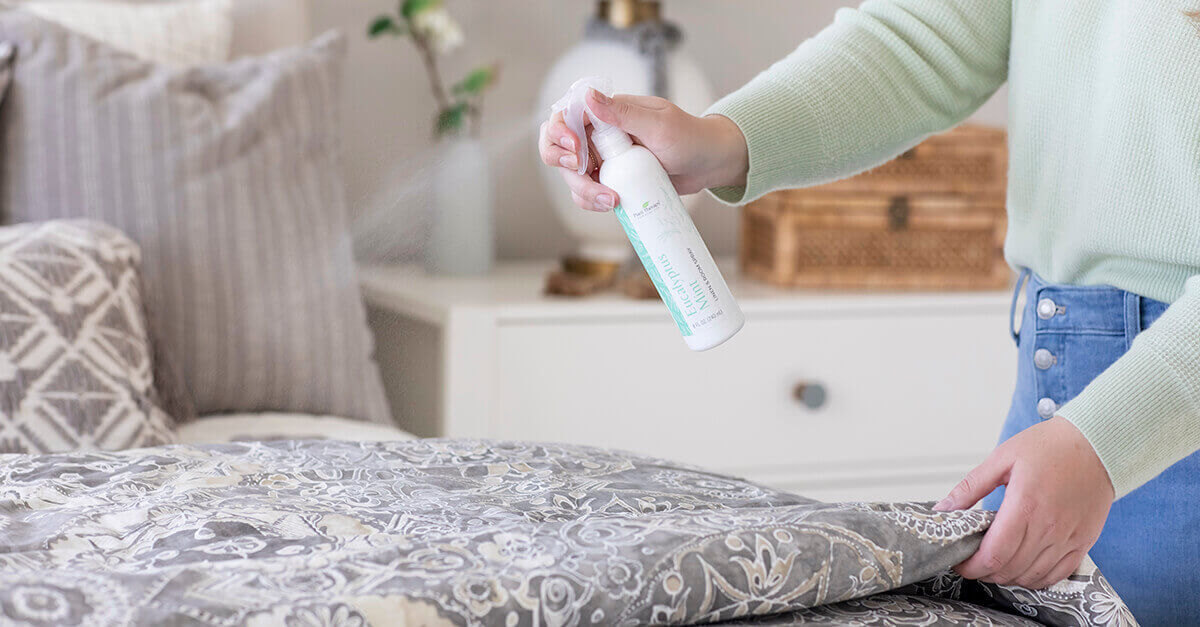 woman spraying linen and room spray on her bed
