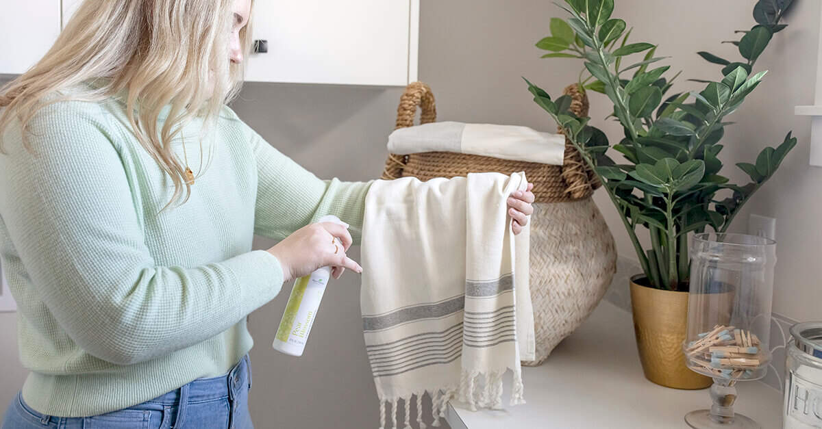 A woman spraying her towel with linen and room spray