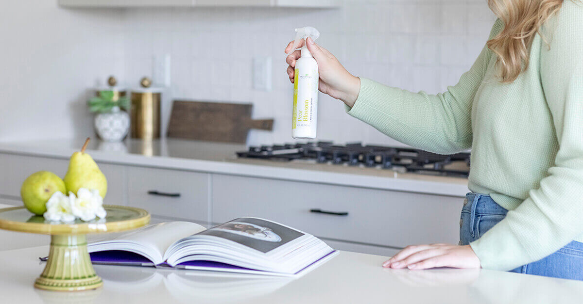 a woman spraying room spray in the kitchen