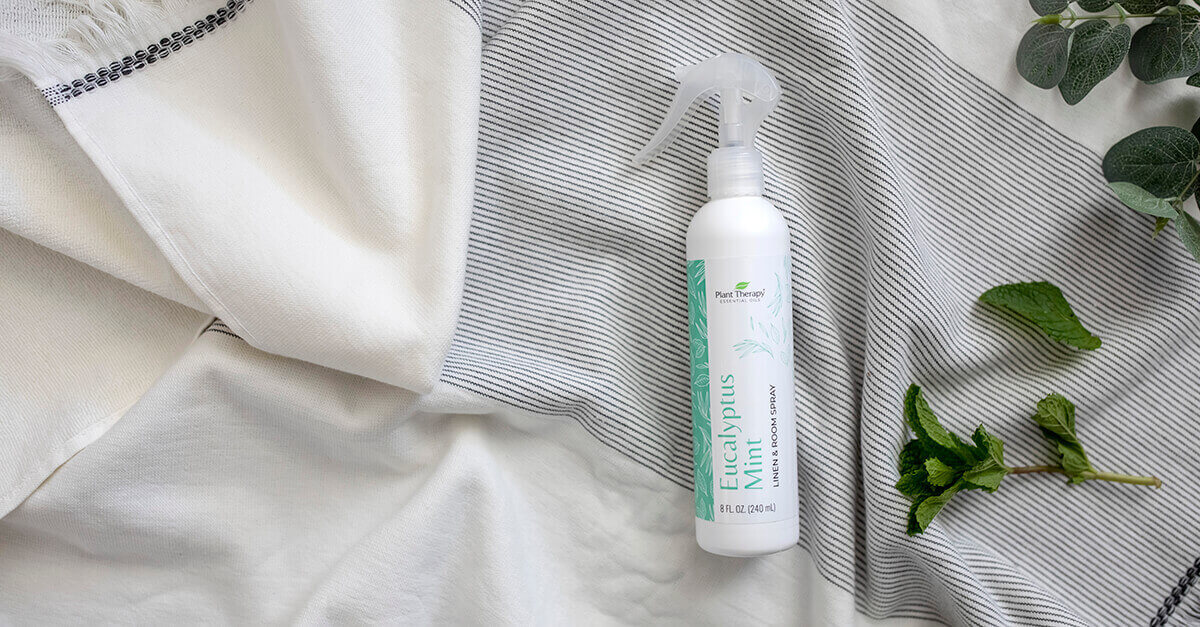 bottle of linen spray laying on sheets