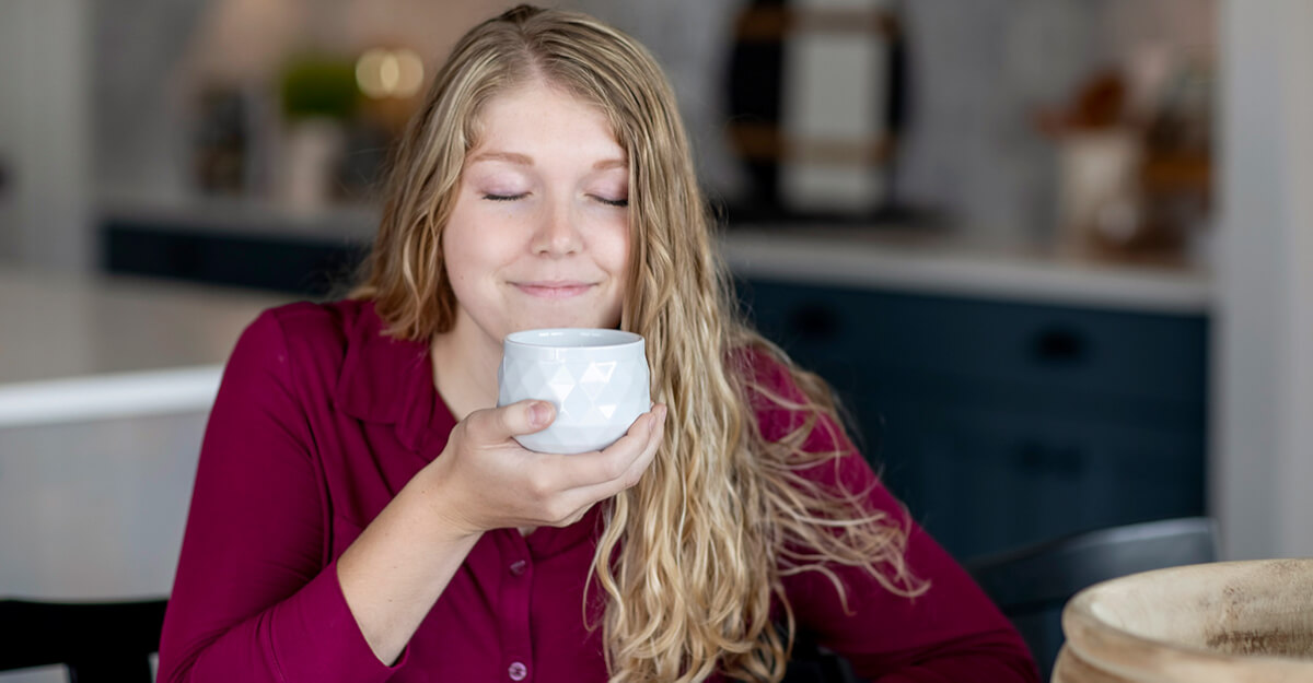 young woman smelling a candle