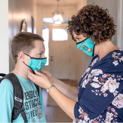 Mother helping her son with a mask