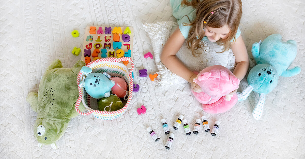 Child playing with stuffed animals with Plant Therapy's KidSafe essential oils laid out on display