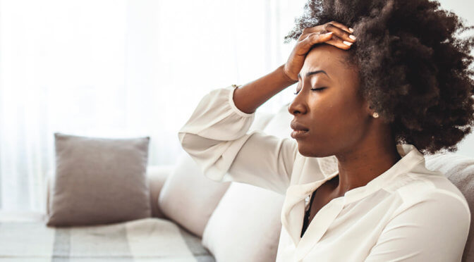 Woman looking stressed, sitting on her couch