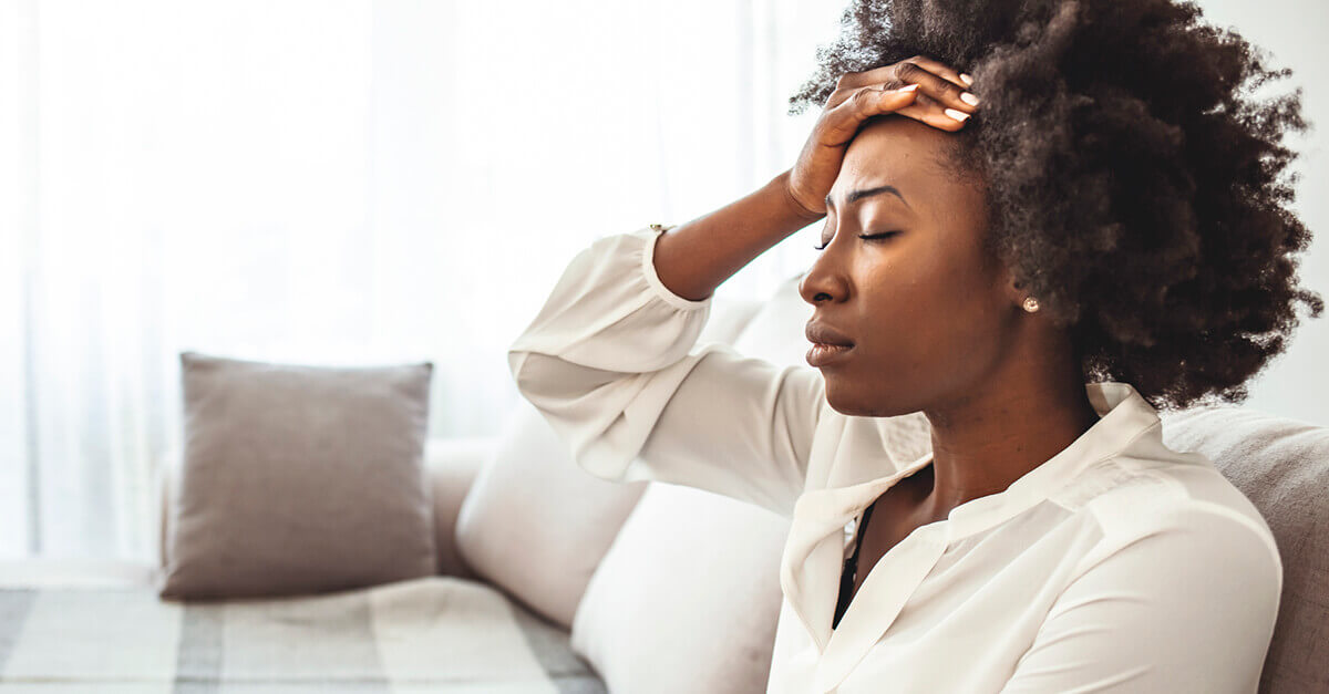 Woman looking stressed, sitting on her couch for mental health awareness month